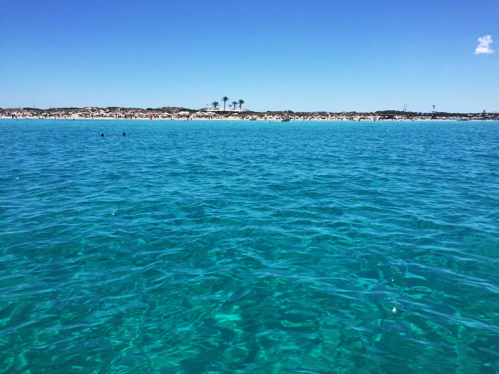 Looking to the Formentera coast from a boat on the bright turquoise ocean