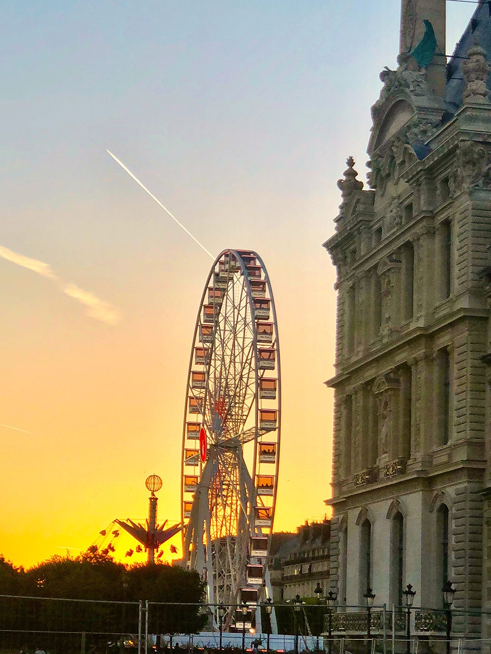 A view of the sun setting behind a Ferris Wheel at The Louvre. December 2018