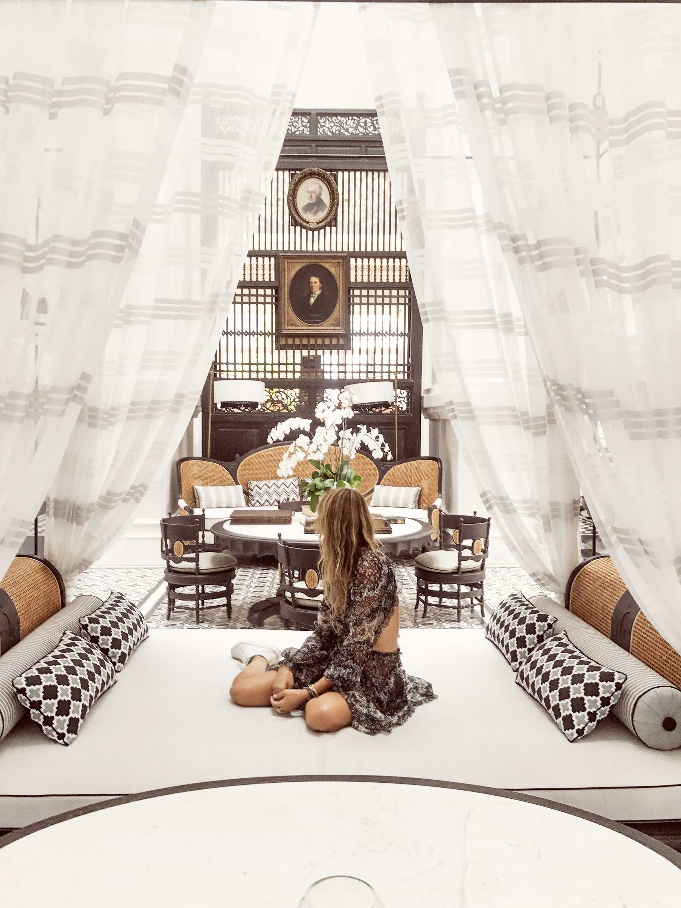 Romy sitting on a large canopy bed with luxurious white curtains and patterned pillows