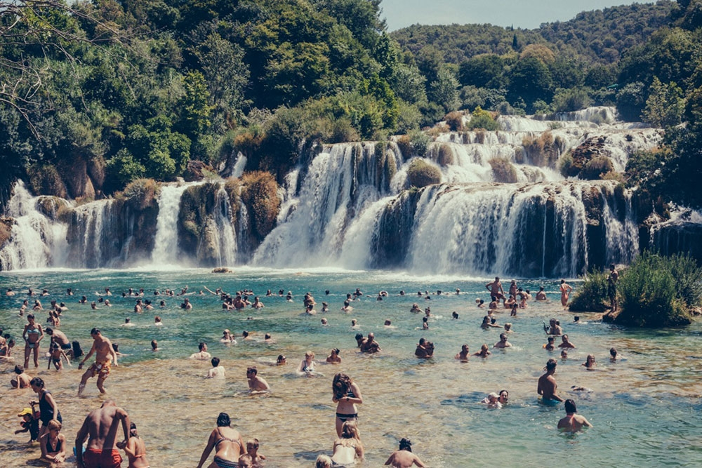 Swimmers embracing the cool water at a waterfall in Krka National Park – Split
