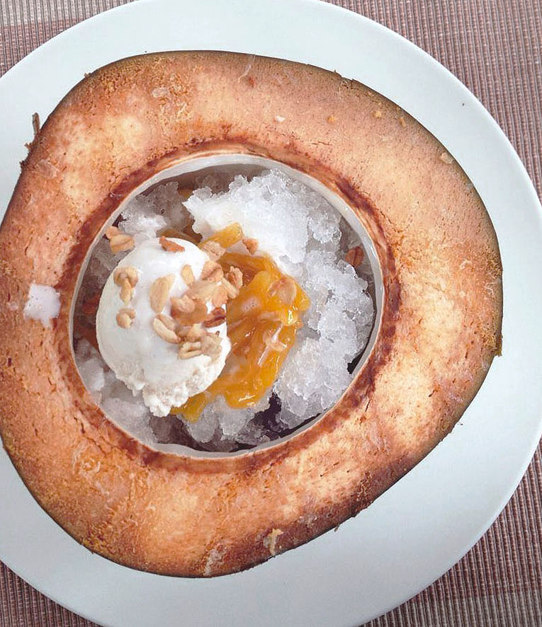 Filipino dessert, Halo Halo, is crushed ice served in a coconut, topped with ice cream, fruit and evaporated milk