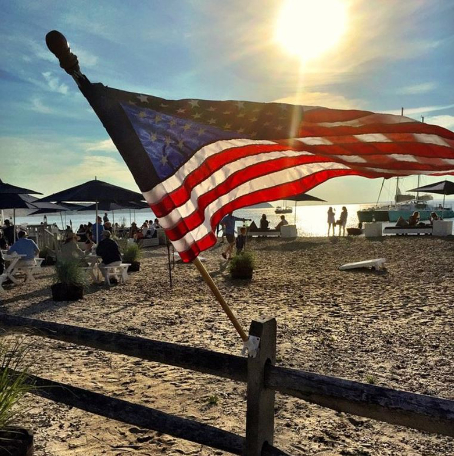 The American flag flying in the wind at a sunny day on the beach