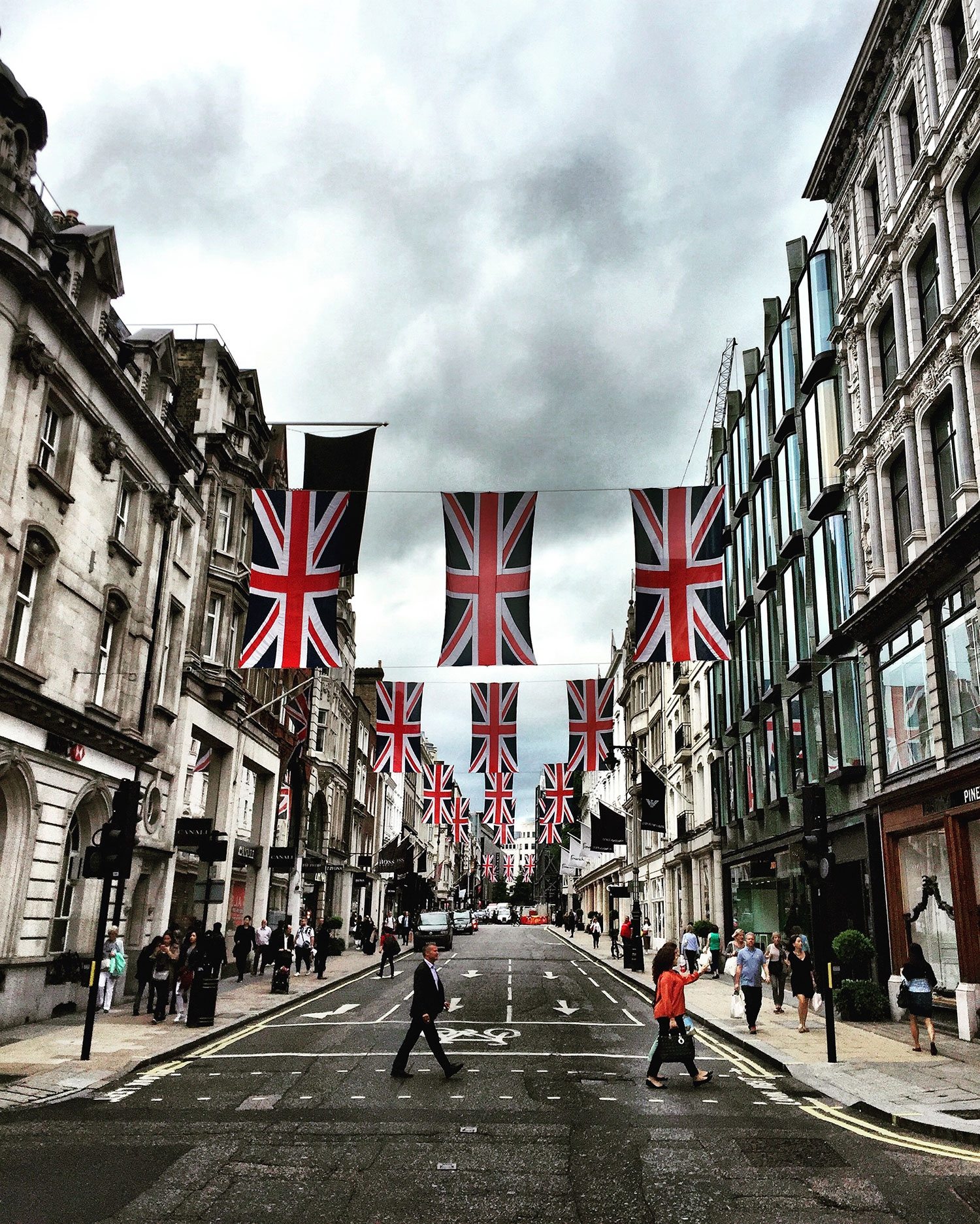 Rows of 3 United Kingdom flags hang across a road in London