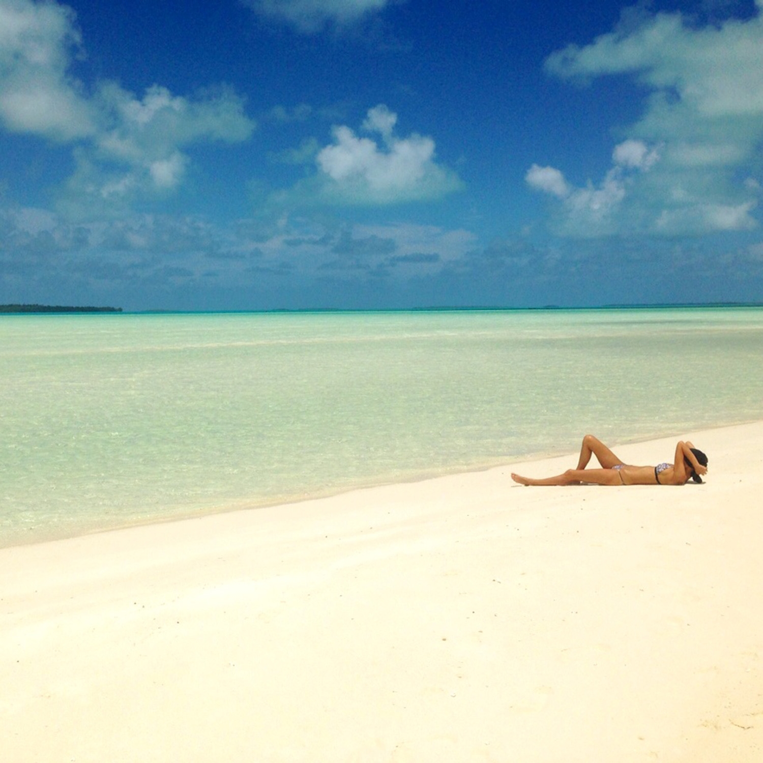 Our model lays along an expansive white beach and looks out across the pale blue ocean