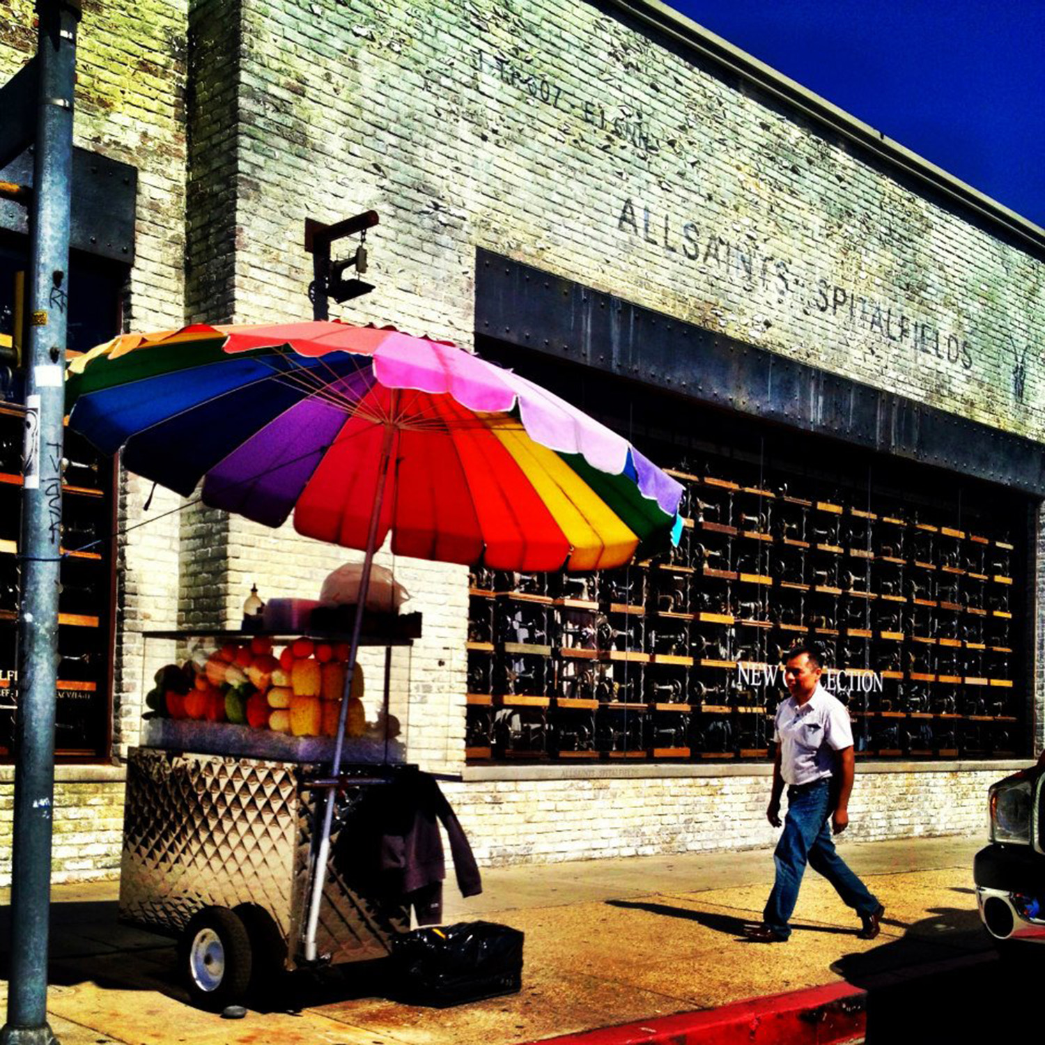 A fruit stall on Robertson shaded by a large rainbow umbrella