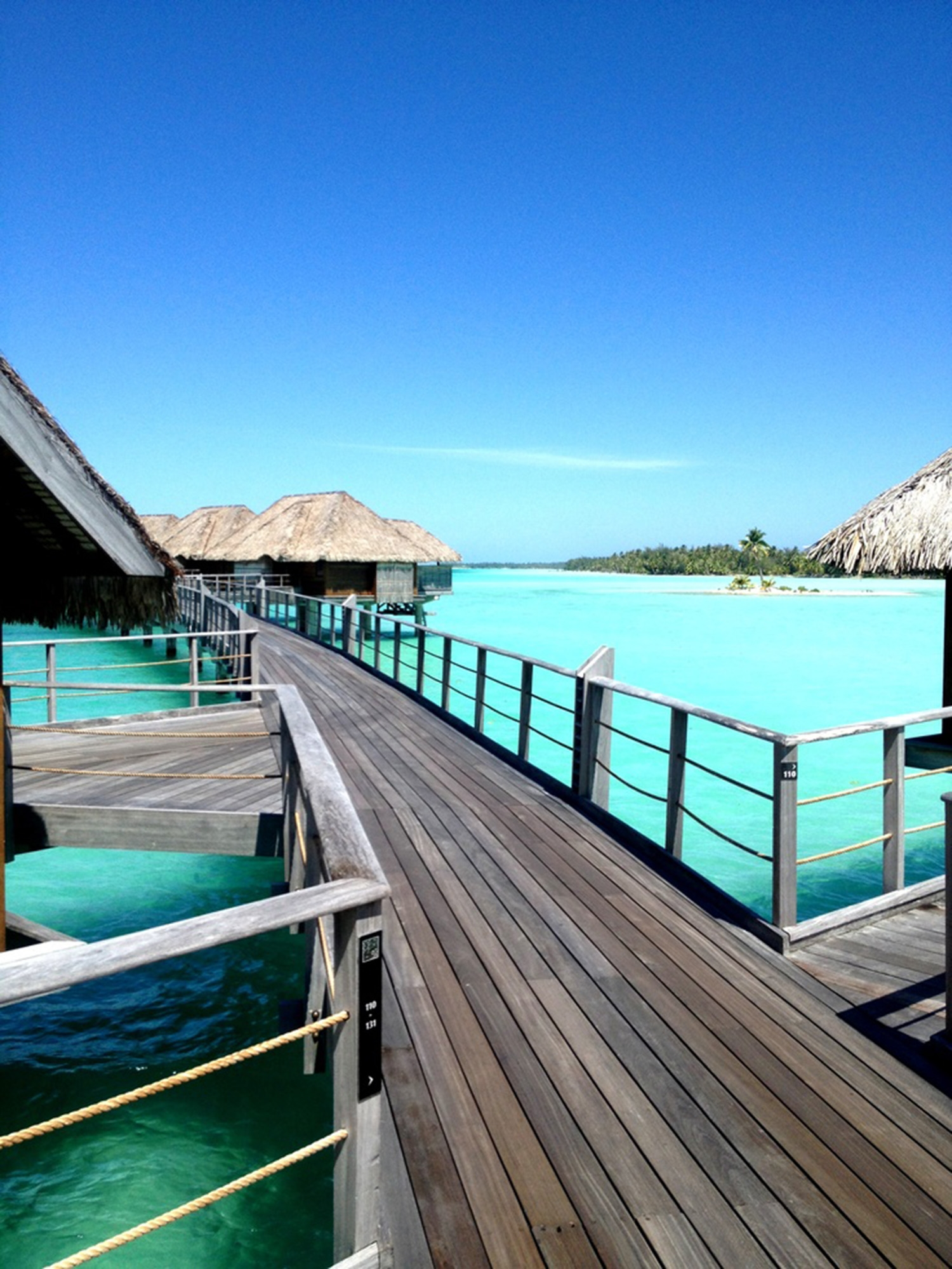 Walking along a wooden walkway connecting a series of villas, floating above the cool blue waters of Bora Bora