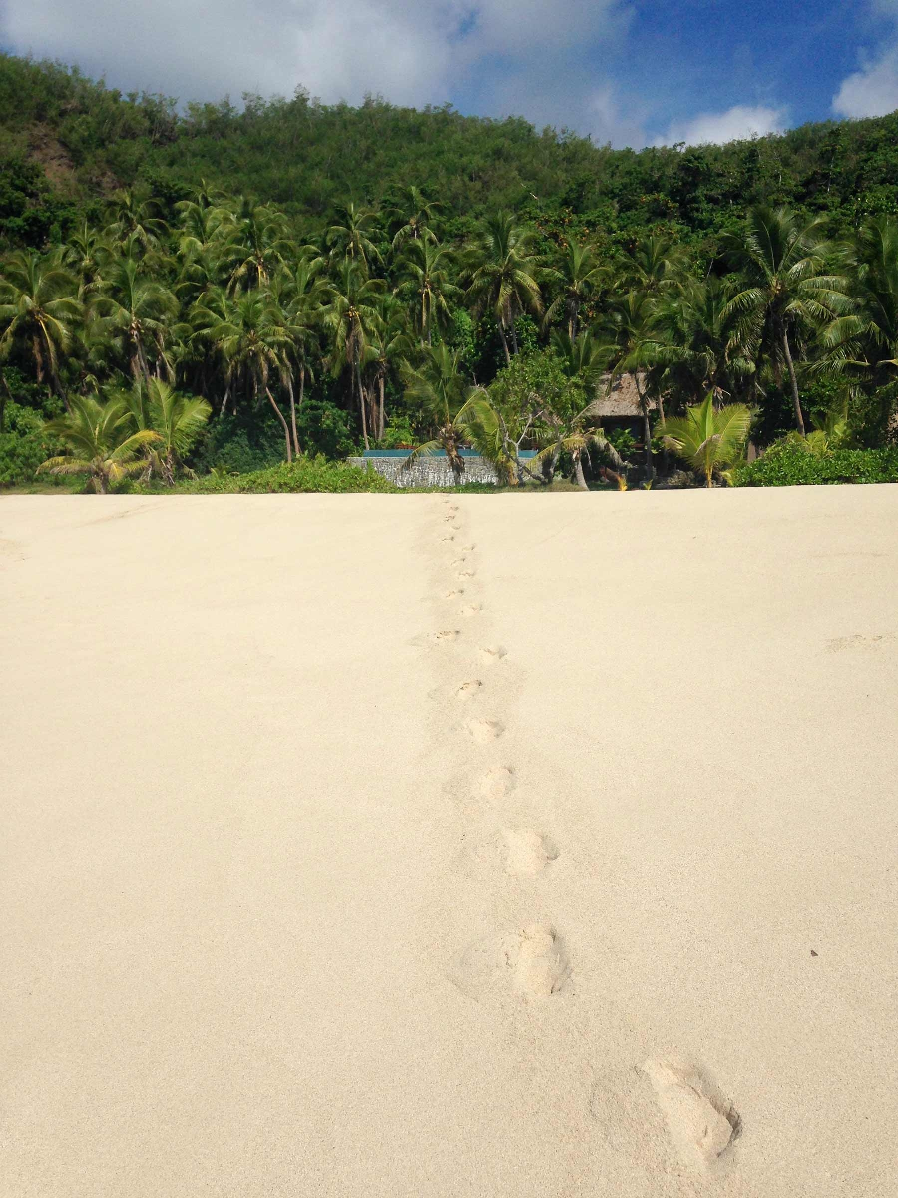 Footsteps through the sand from the mainland to the sea