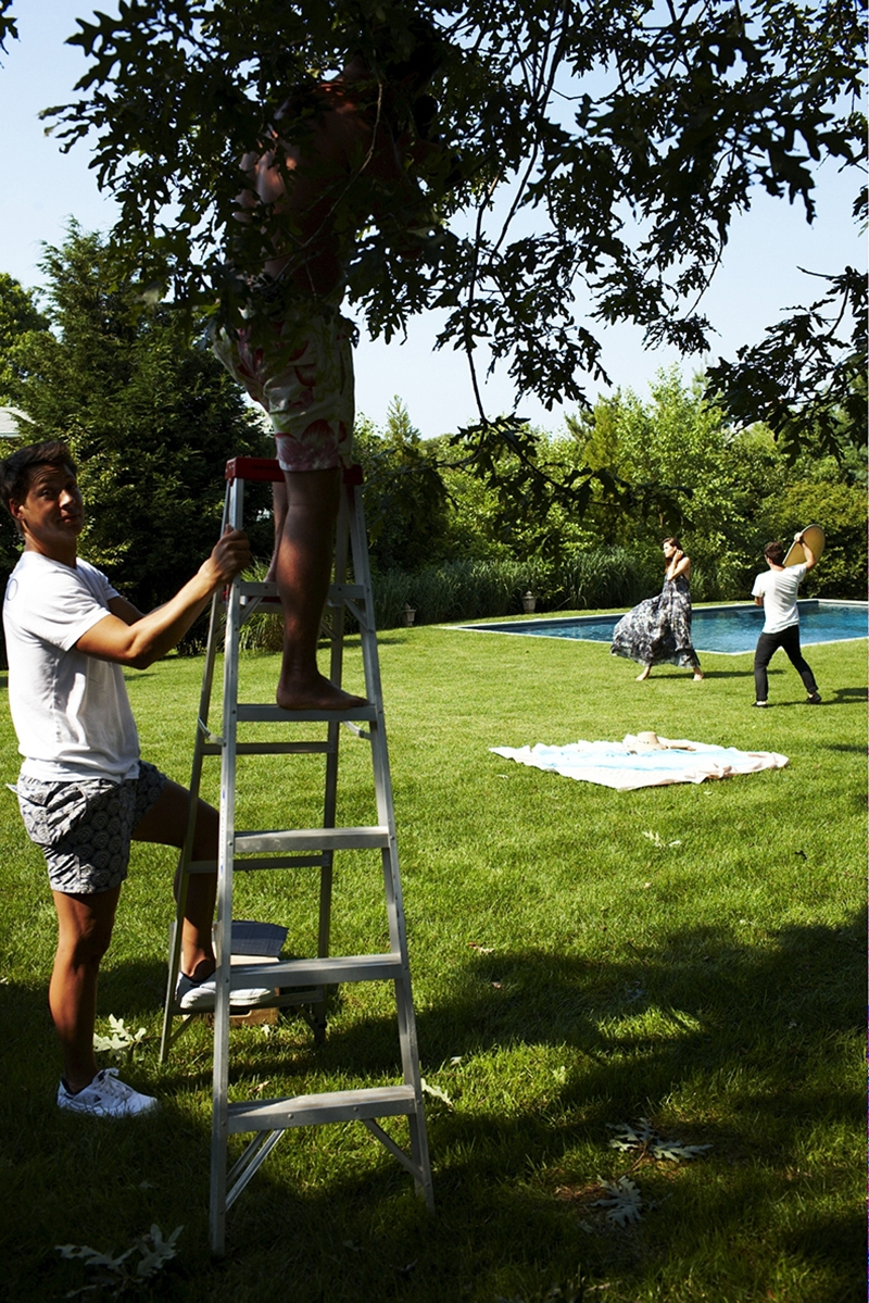 A behind the scenes shot of our 2009 Swim photoshoot – one man holds the bottom of a ladder while the other is stood at the top with his head in the trees