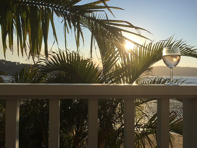 A glass of wine sits on the railing of the balcony at Barrenjoey Villa as the sun sets over the sea and mountains ahead