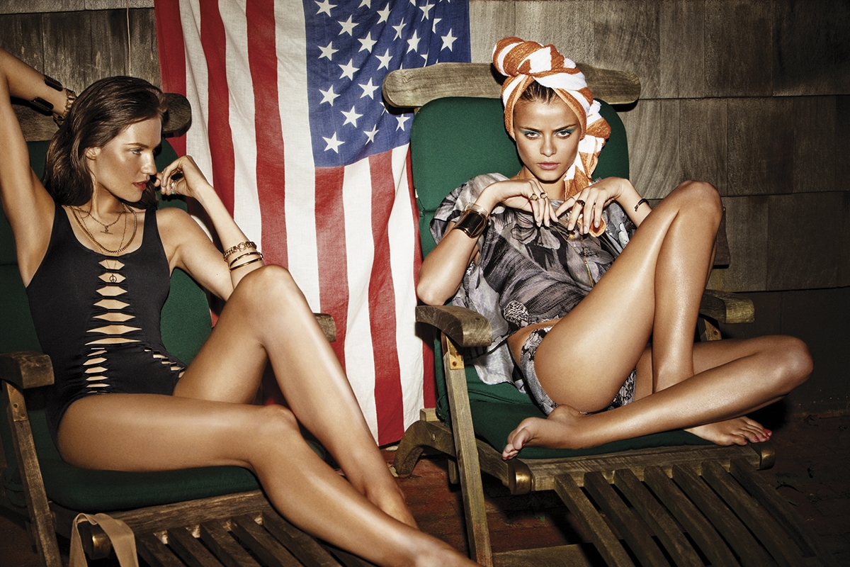 An image from our 2009 Swim Campaign with two models sitting on chairs in our swimwear in front of the American flag