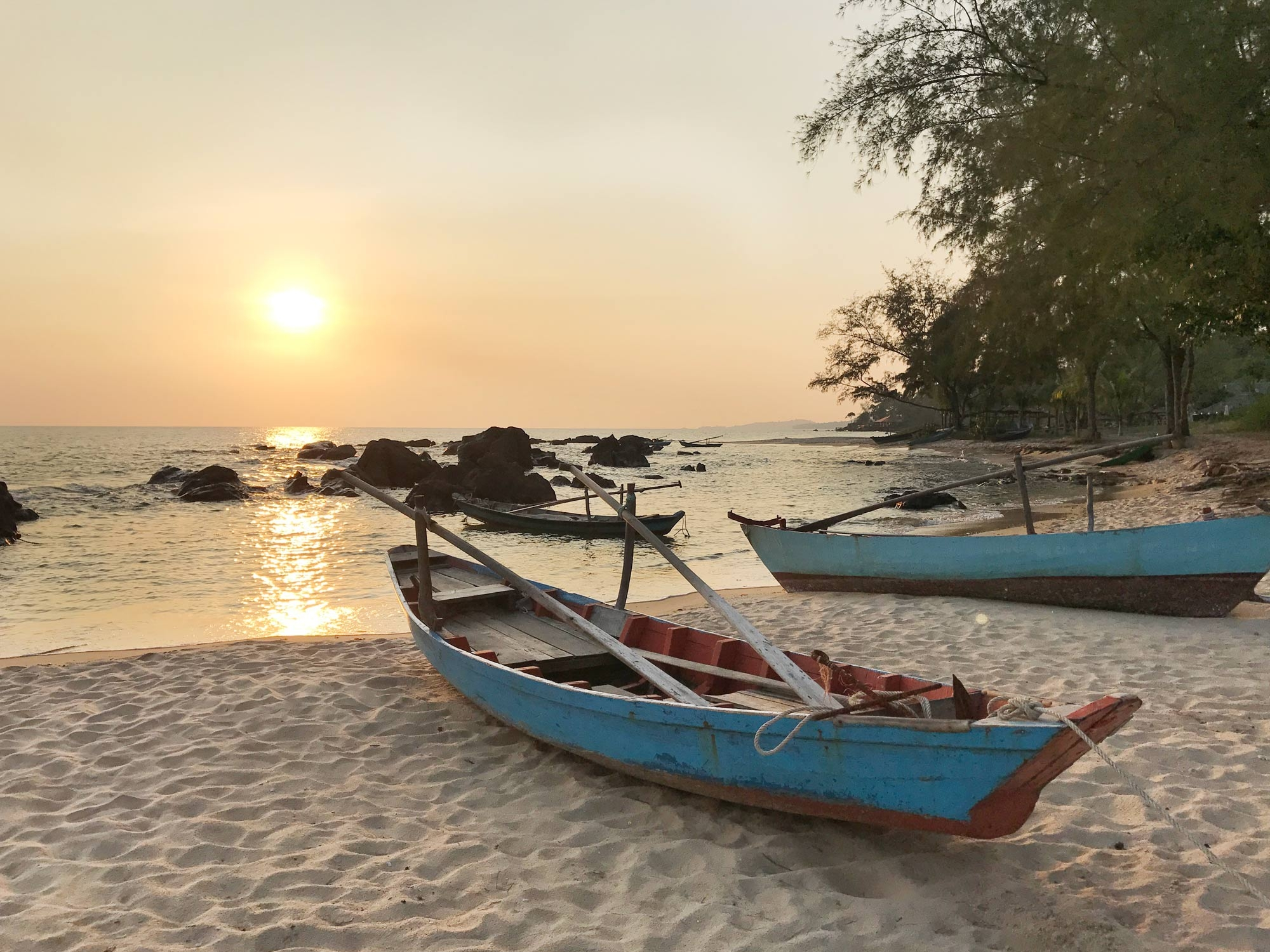 Vietnamese row boats sit on the shoreline as the sun sets over the horizon