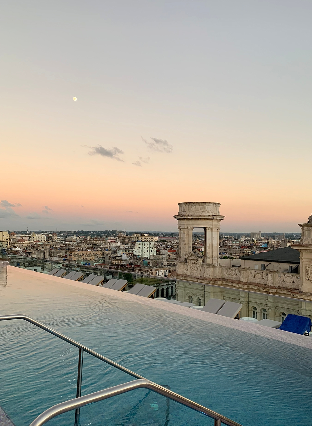 The sun sets over Havana from a rooftop pool