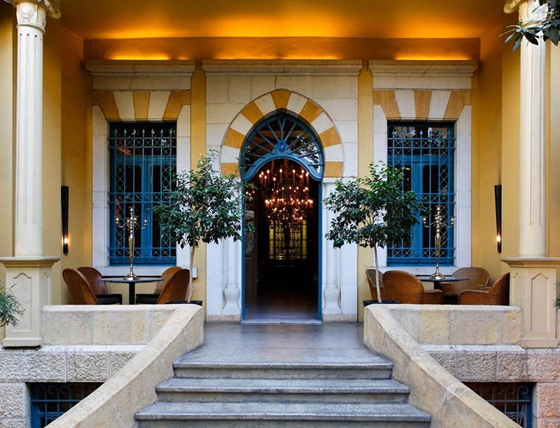 The entrance of Hotel Albergo Beirut boasts a stone staircase, yellow exterior, an arched door and blue finishes on the windows and arch