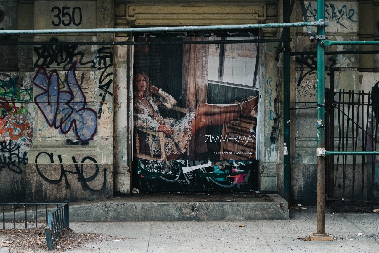 A large Zimmermann campaign image surrounded by graffiti on a New York street