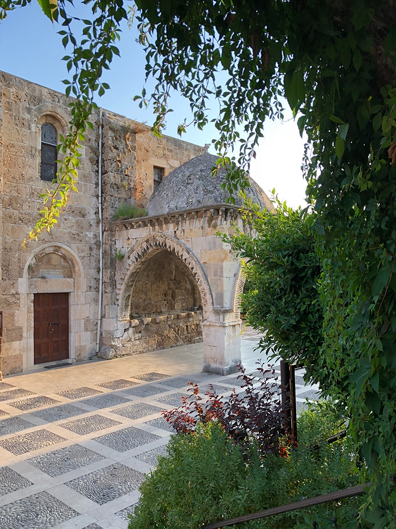 A stone building connected to archways with a dome roof in Byblos