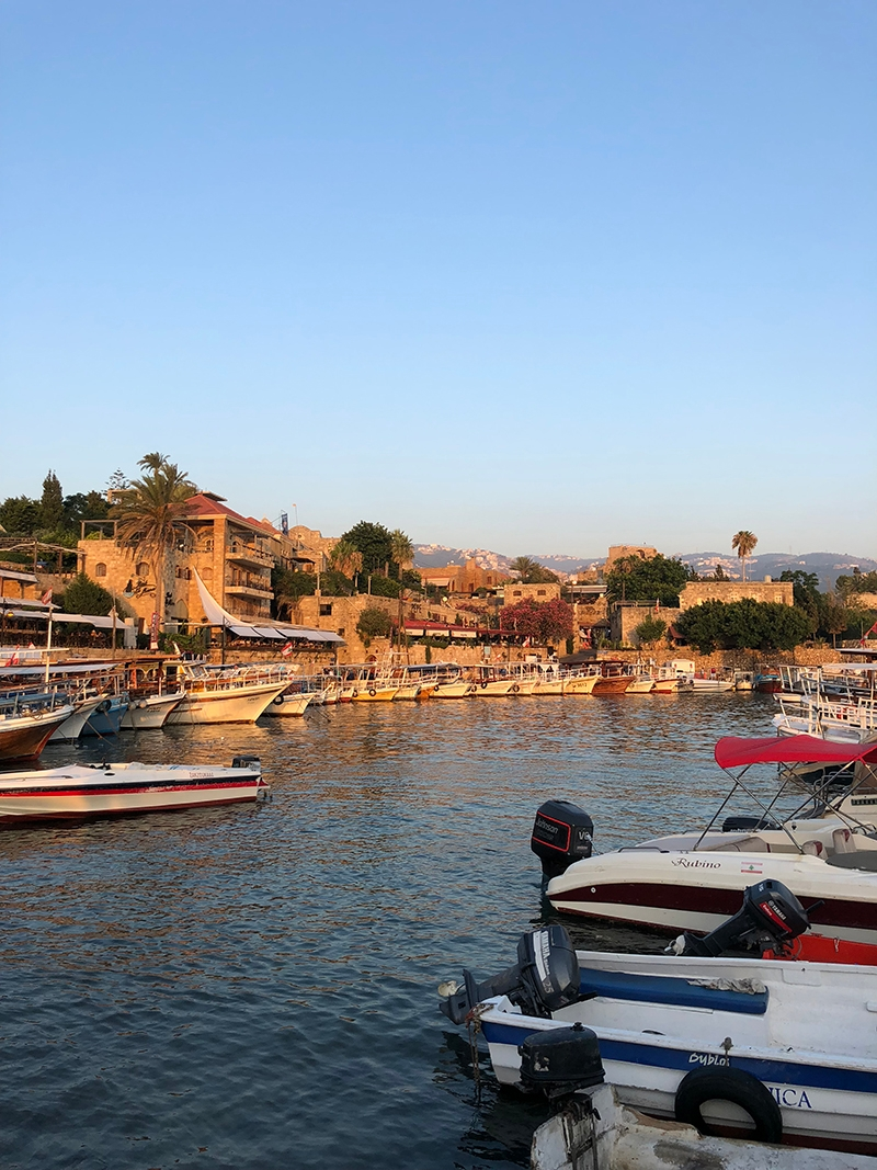 Down by the water, surrounded by boats and stone buildings in Jbeil