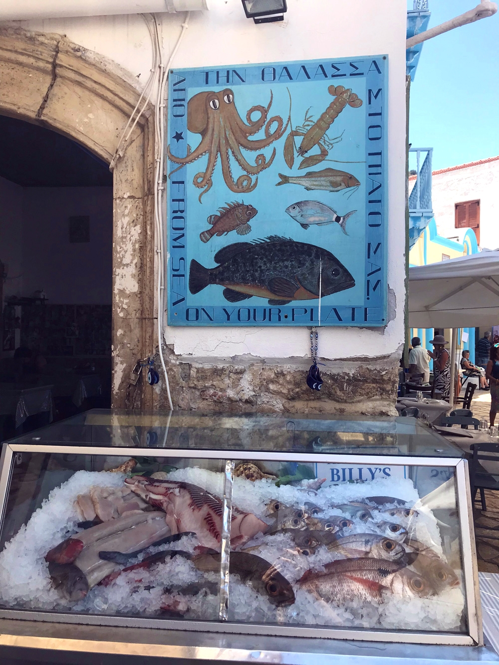 Freshly caught fish in an icebox below a poster advertising fresh octopus, fish and crustaceans on the streets of Kastellorizo
