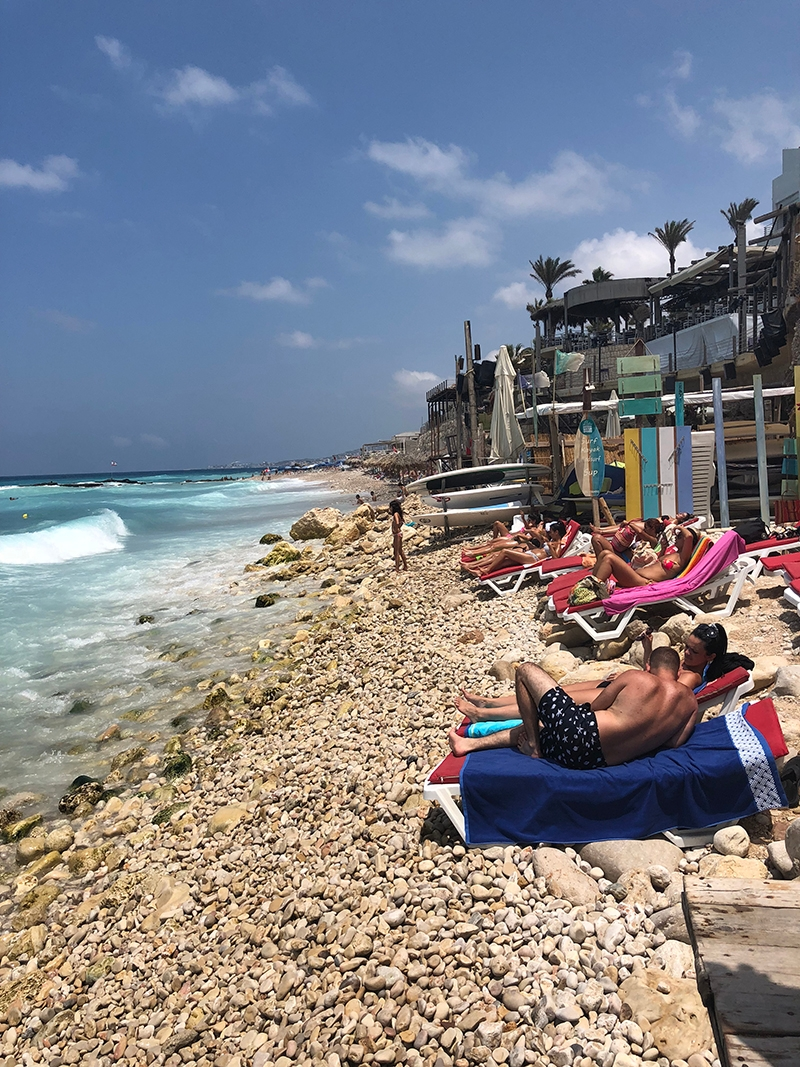 On the beach in Batroun with a stone shoreline and bright blue water