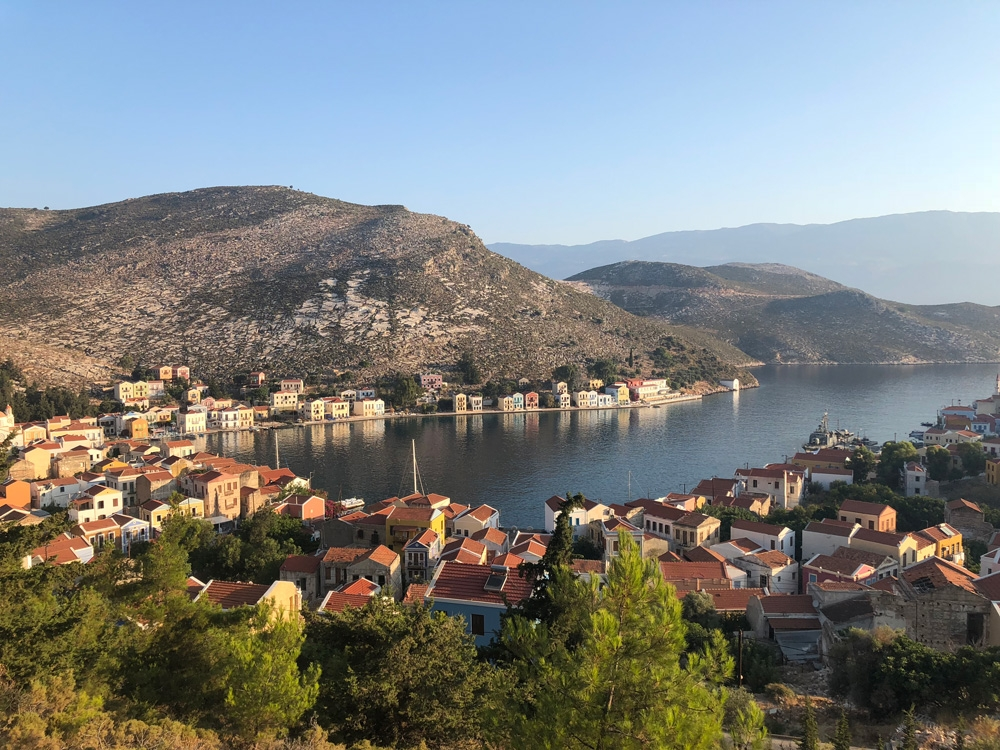 The view of houses and fauna along Kastellorizo Harbour from atop a mountain