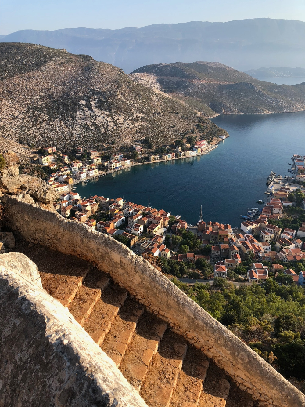 From an old stone staircase on the side of a mountain, enjoy the coastal scenery that encapsulates the calmness and beauty of the seaside town