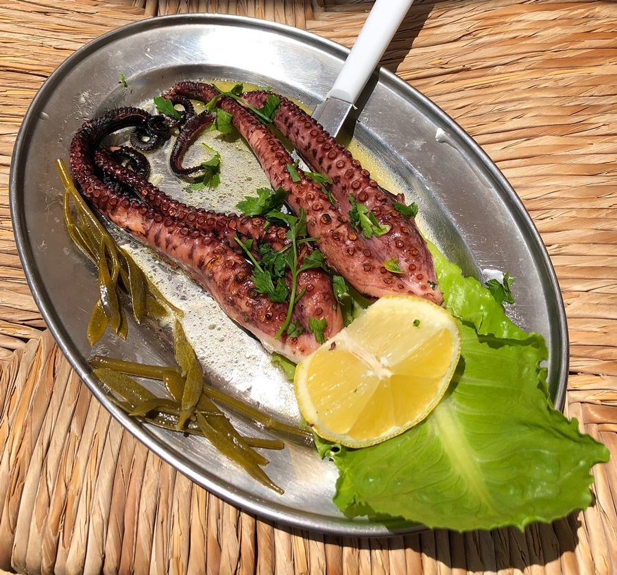 A plate of octopus tentacles and lemon is offered for a simple Greek lunch