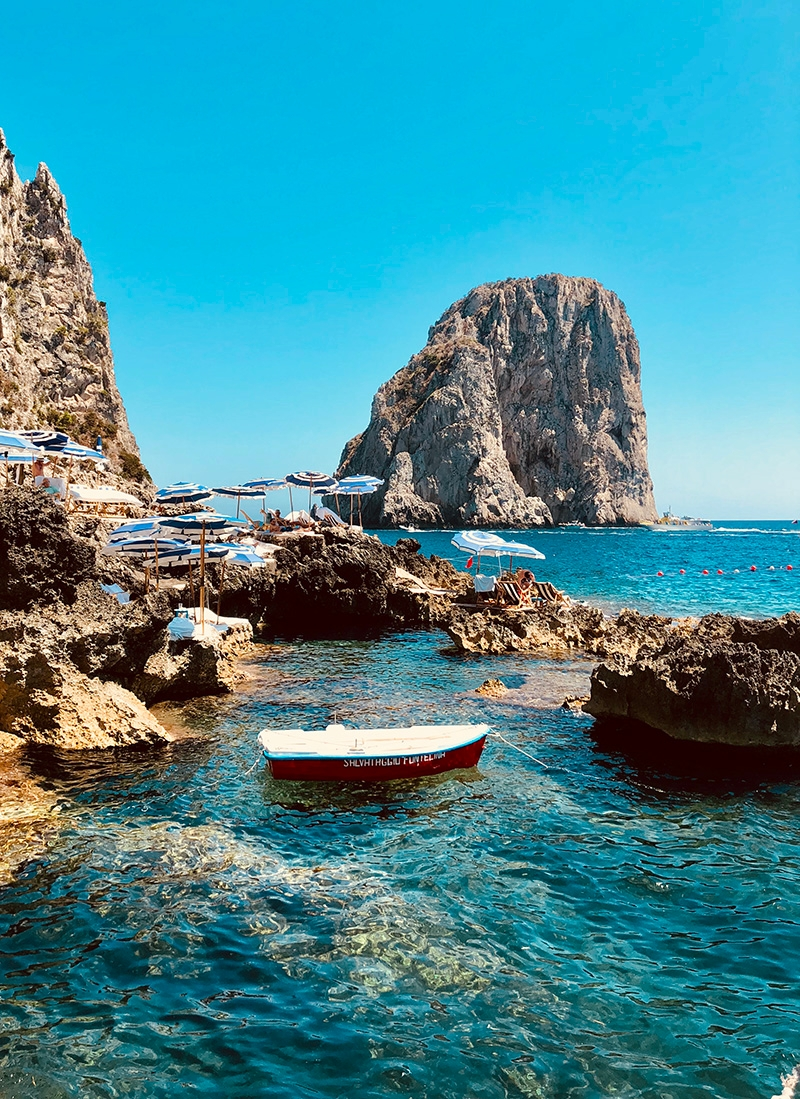 Faraglioni rocks scattered around the Capri coast, with white and blue umbrellas perched upon them for shade