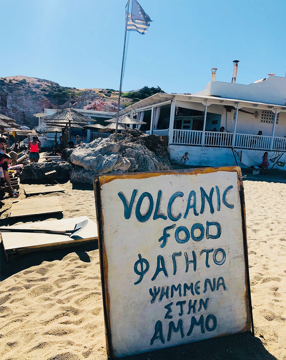 """An image of Sirrocco taverna at Paliochori Beach. A small white house with a wrap around verandah and Greek flag raised. A sign in the sand reads, """"Volcanic Food"""", as well as four lines of Greek writing."""