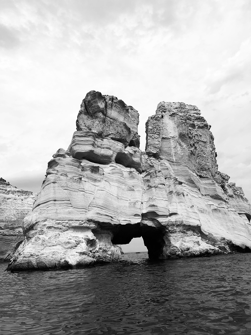 A black and white image of a large rock arch in the ocean with a divide that continues halfway down the centre.
