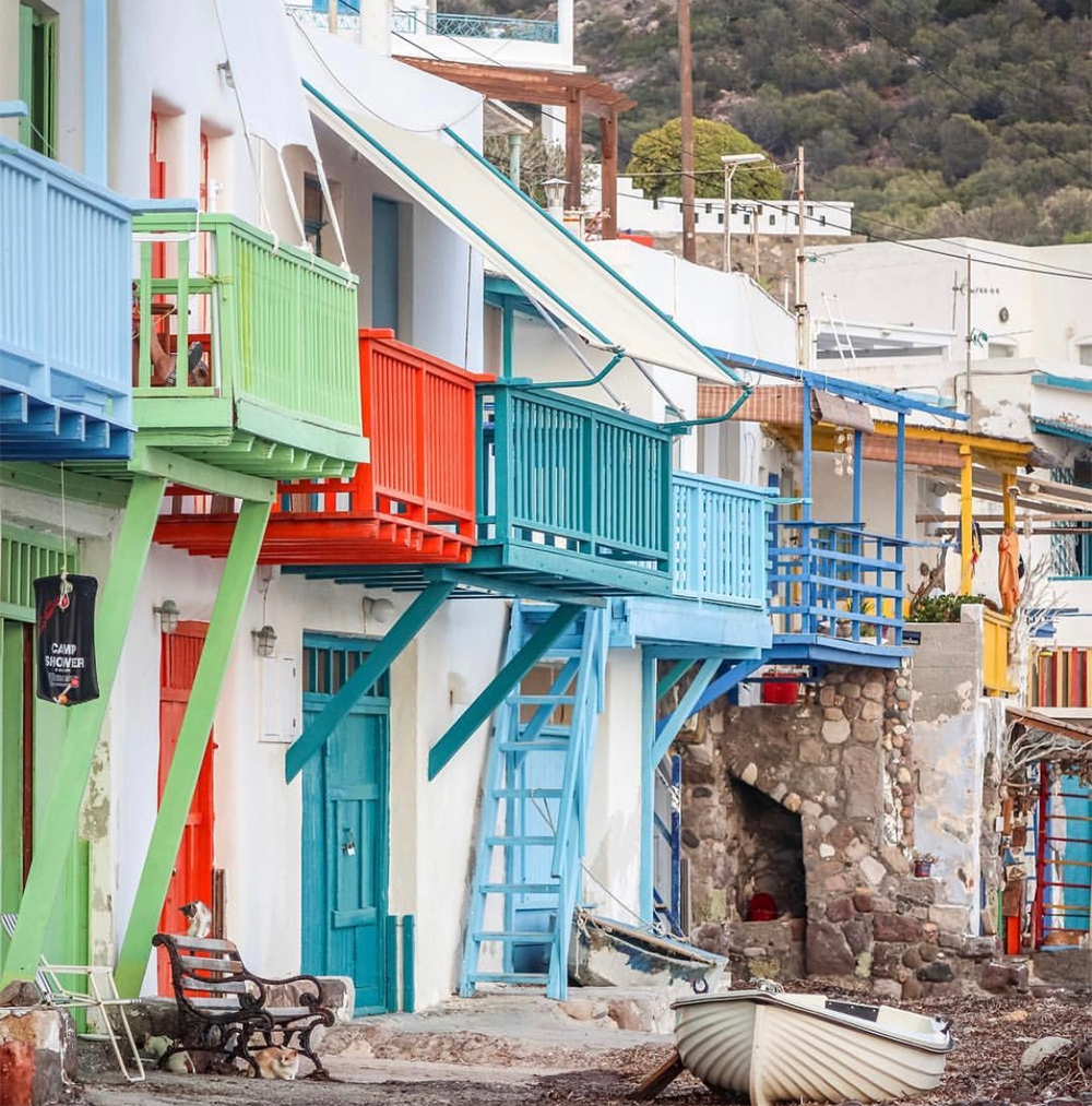 White stone houses finished with bright blue, green and red balconies line the streets of Milos.
