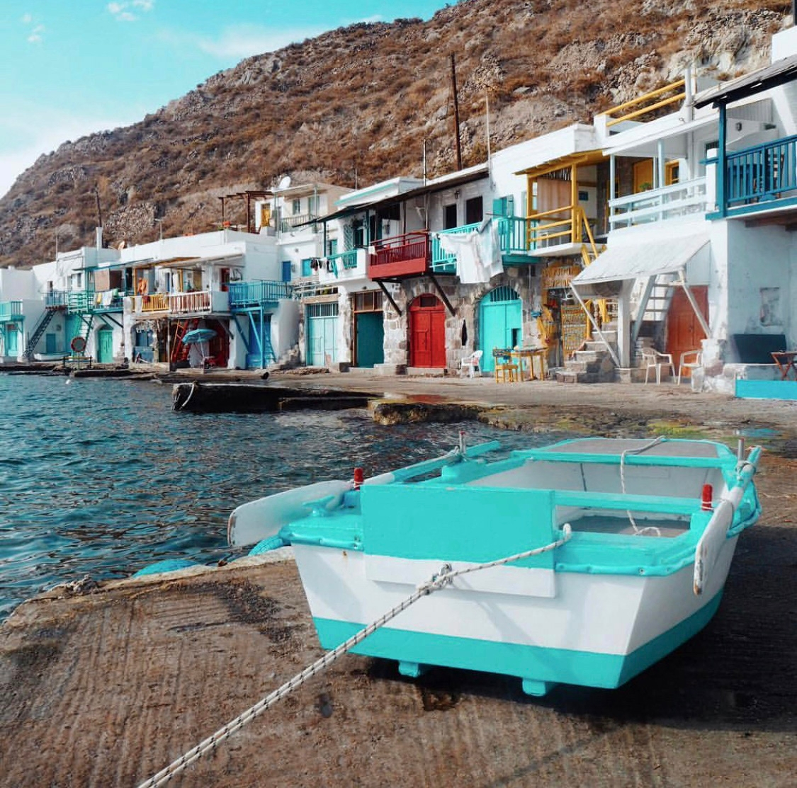 White houses with colourful finishes line the coast of the fishing village, and a bright turquoise and white boat is berthed on a concrete dock.