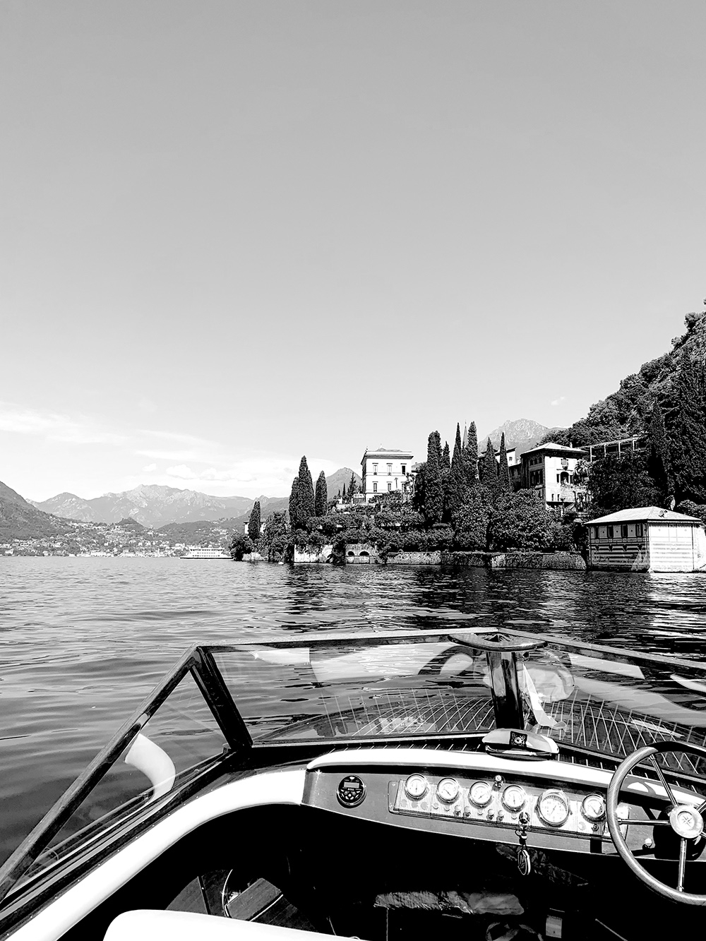 A black and white image taken from a boat anchored on the lake, highlighting the tall trees, dense shrubbery and classic Italian buildings ahead.