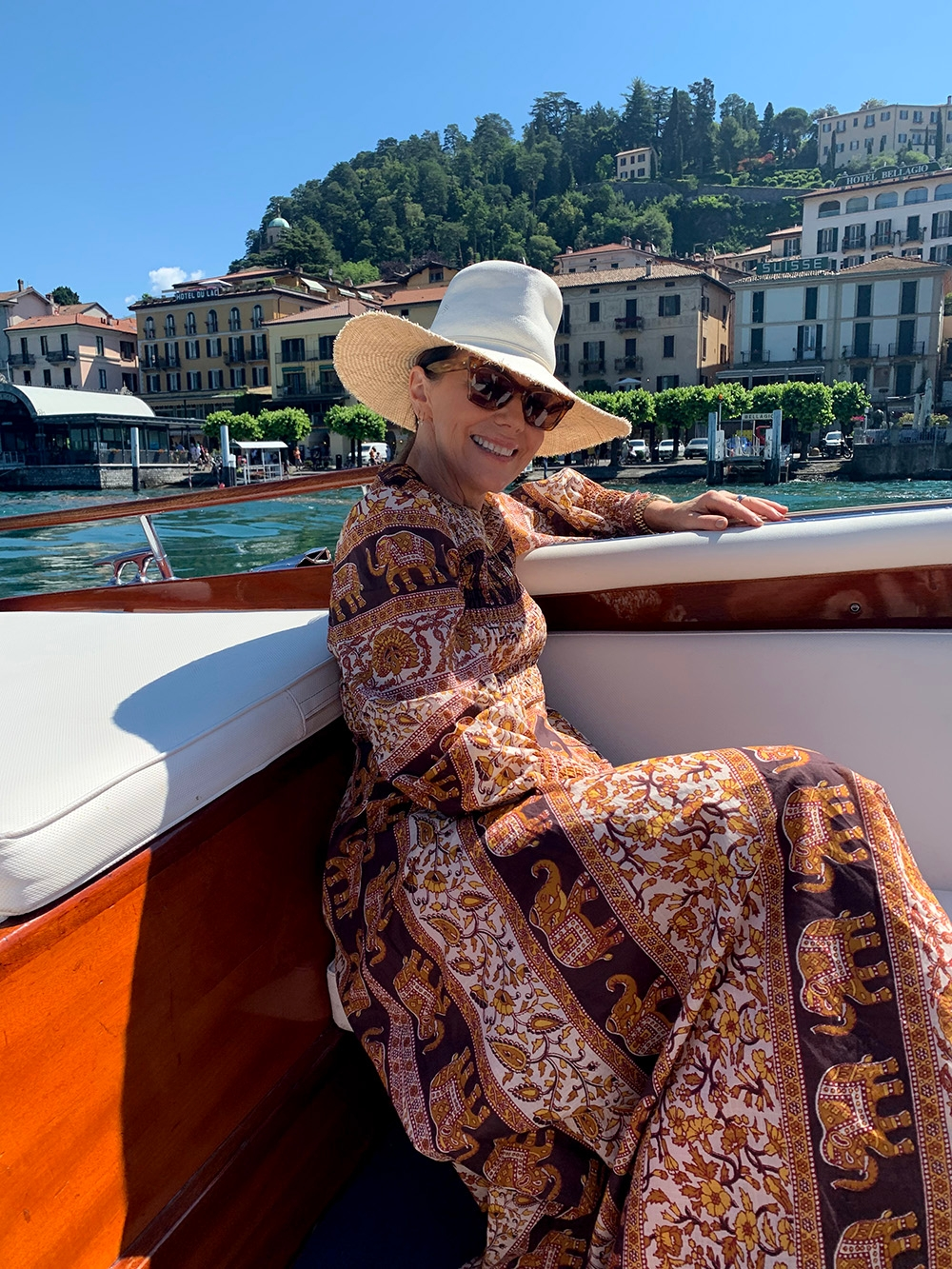 Nicky Zimmermann admiring the buildings along the Lake Como shoreline from a boat on the water. She wears the Suraya Shirred Chevron Dress, a white straw hat and tortoise shell sunglasses.