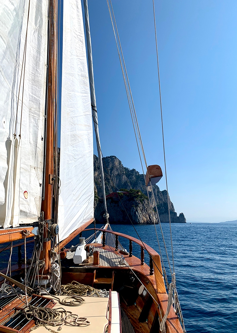 The view from aboard a sail boat displays the deep blue ocean, a large sea stack and the bright white sails and timber finishing of the bow of the boat.