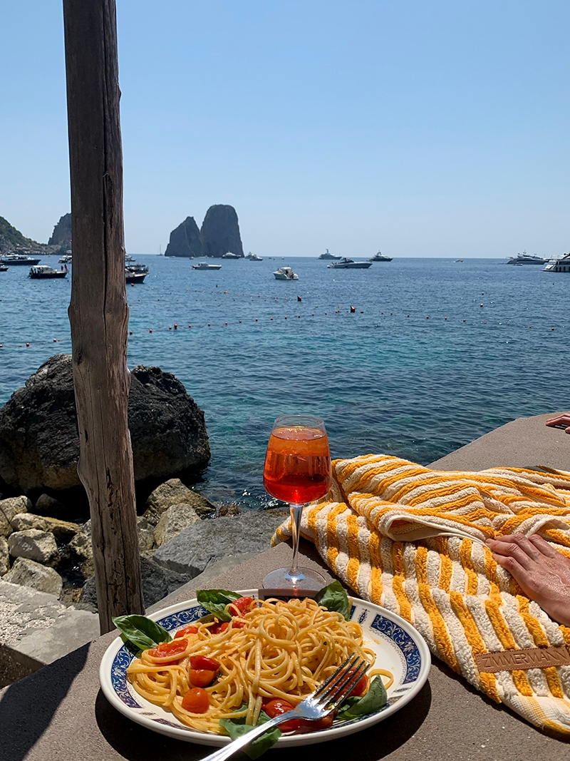Lunch in Capri involves a plate of pasta and an Aperol Spritz while watching the boats by the water.