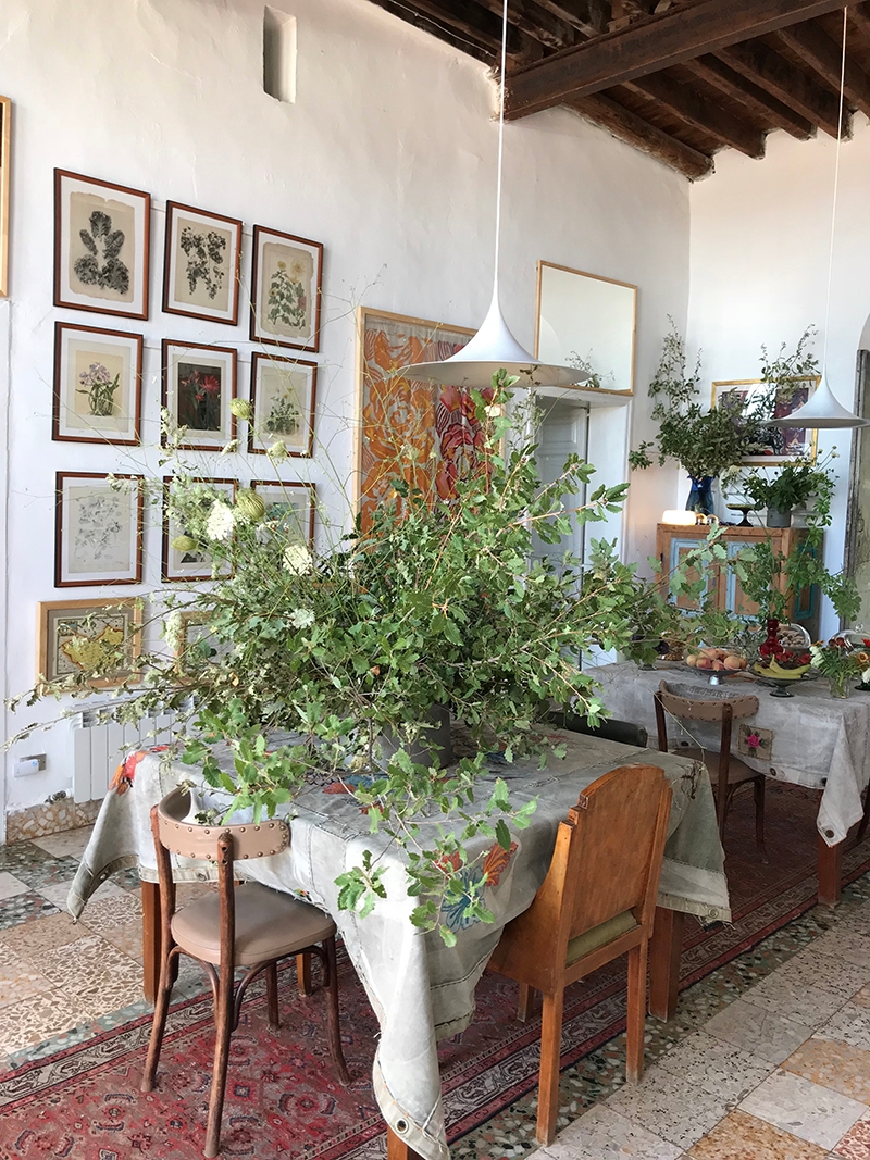 The interior of Beit Douma Villa sees large fauna arrangements as table centerpieces  and framed images gridded on the wall