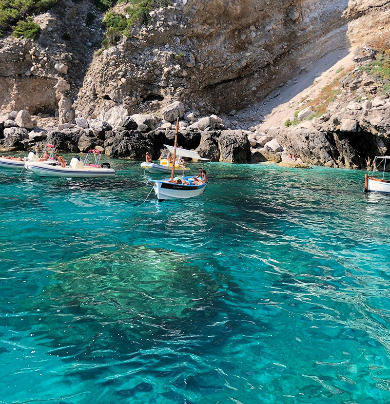 Five small boats have gathered in a cove with bright turquoise water and a rocky shoreline.