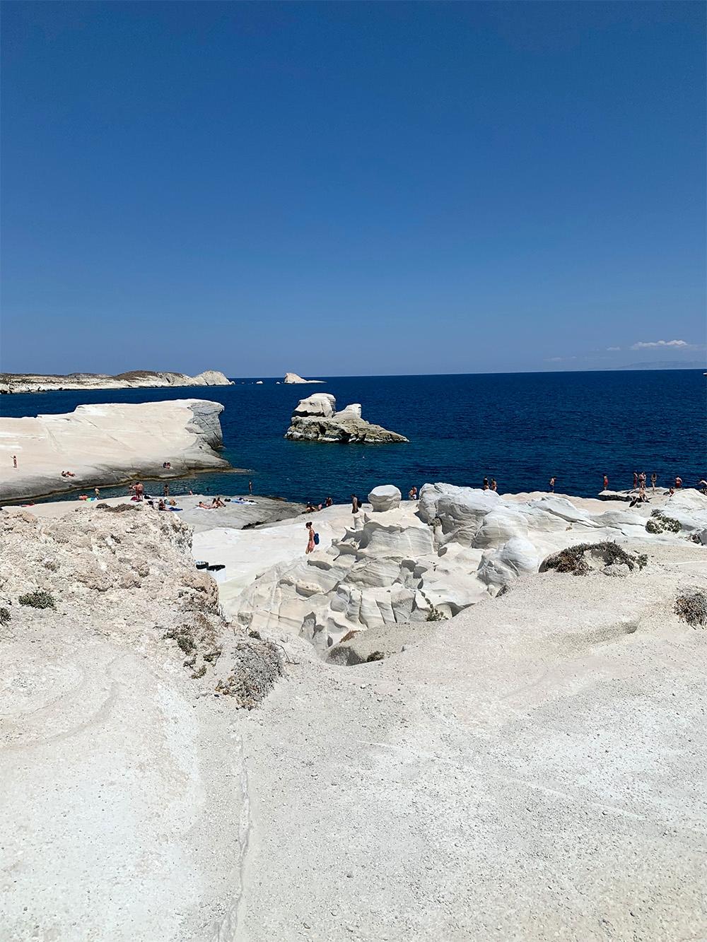 Cliffs over the Sarakiniko coast face the deep blue ocean and clear sky.