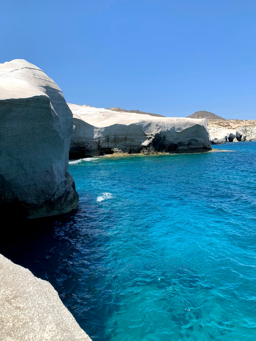 The coast of Sarakiniko Beach, where the bright blue water meets the white volcanic rock which is shaped similarly to a moonscape.