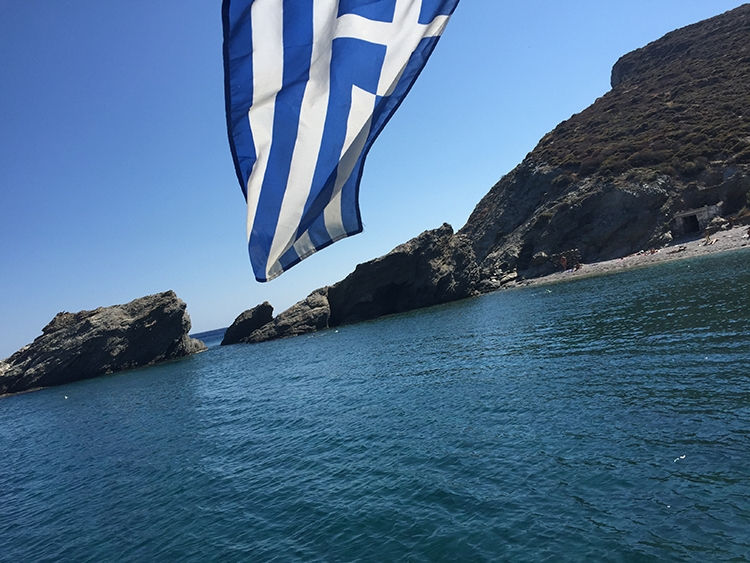 A Greek flag drifting in the wind looking out towards the cliffs of Folegandros