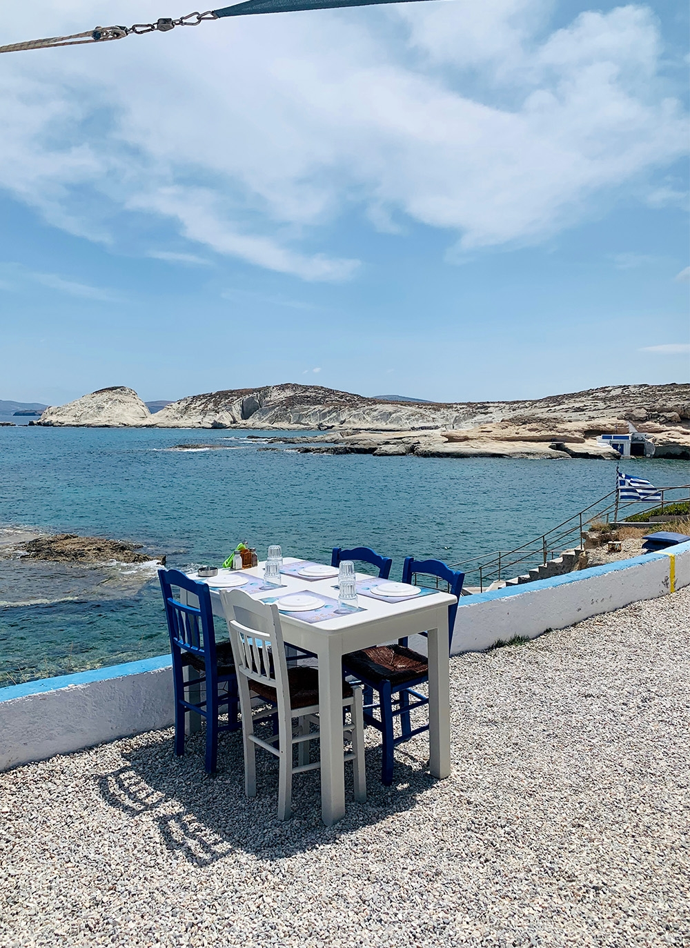 A single white table sits next to the ocean, set with plates, cutlery and glasses ready for lunch.