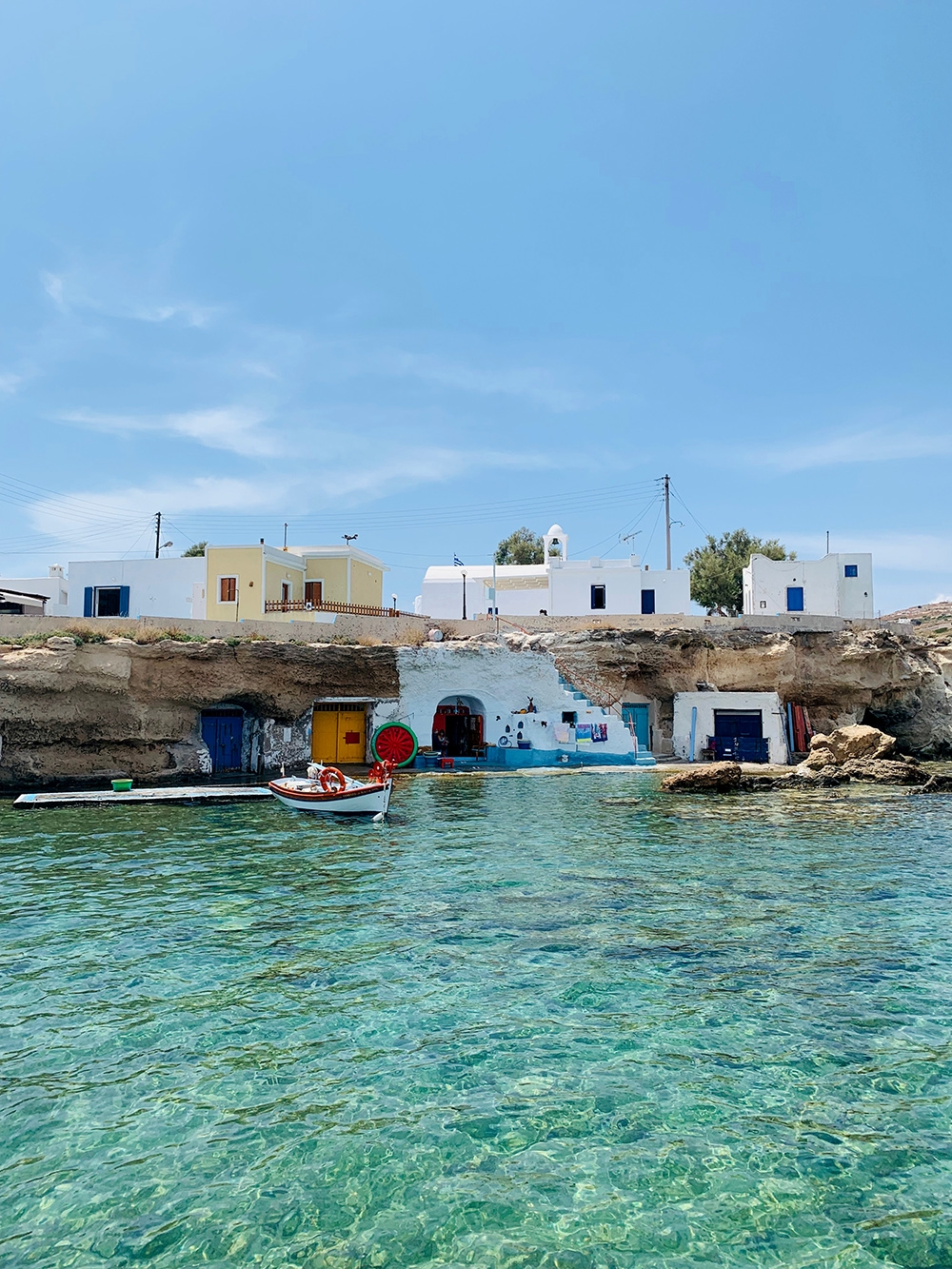 Coulourful houses built into the rocks of the coastline overlook the gleaming turquoise waters.