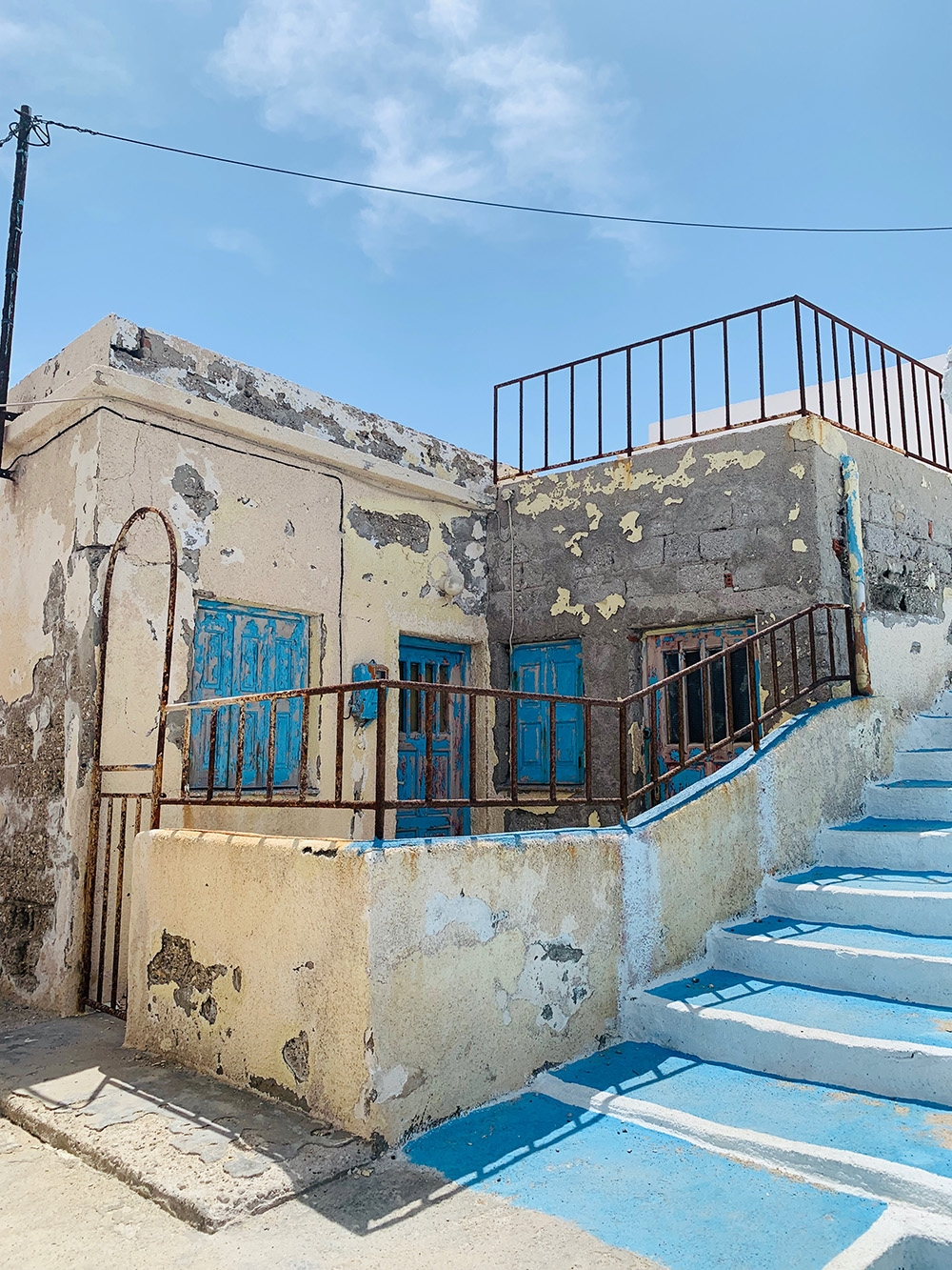 An old Greek building with peeling cream and blue paint on the walls, doors and railings. A blue staircase ascends to the second level.