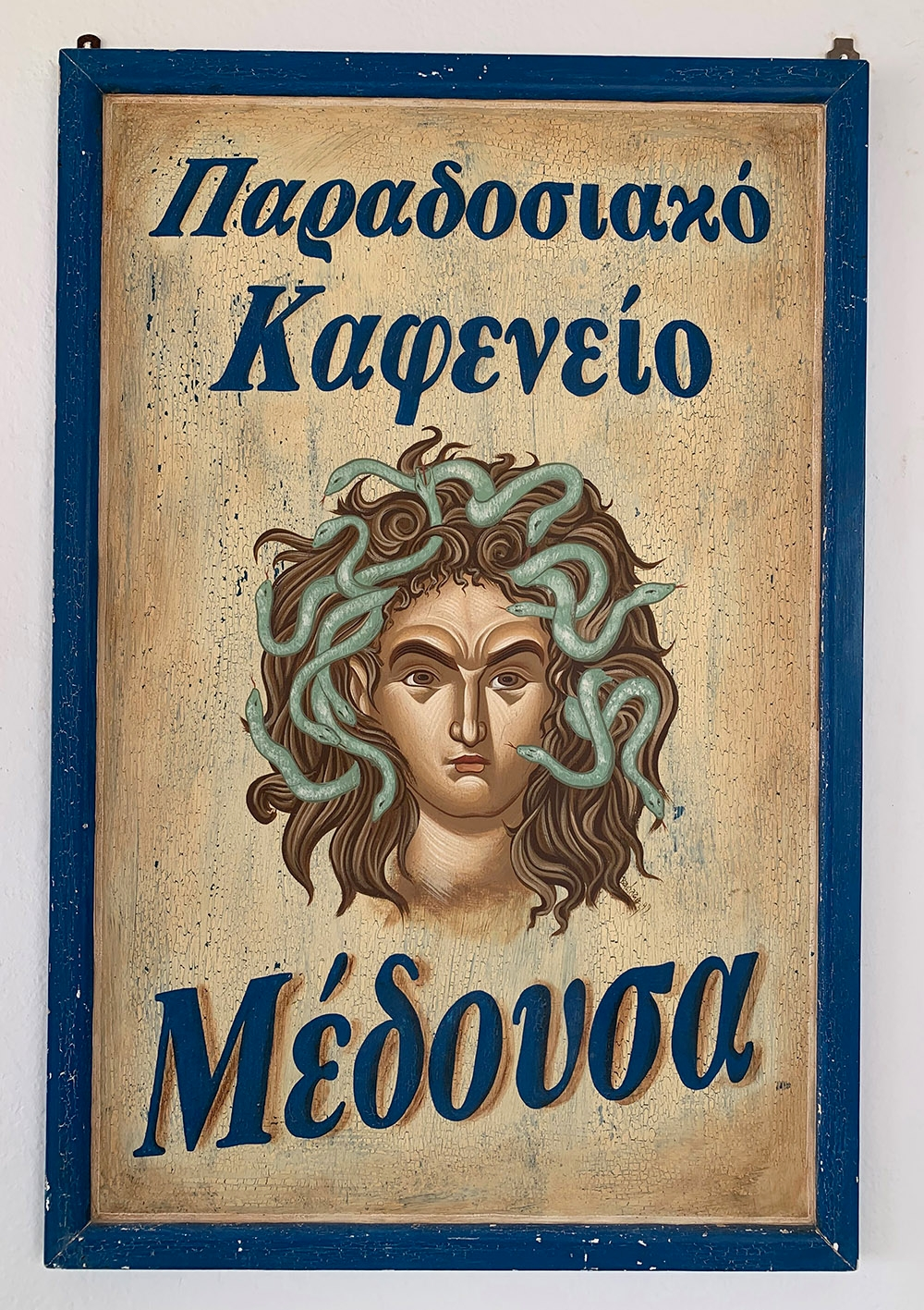 "A Greek sign at Medousa Restaurant in Mandrakia, with a hand painted take of Medusa. ""Simple, Traditional and Delicious""."