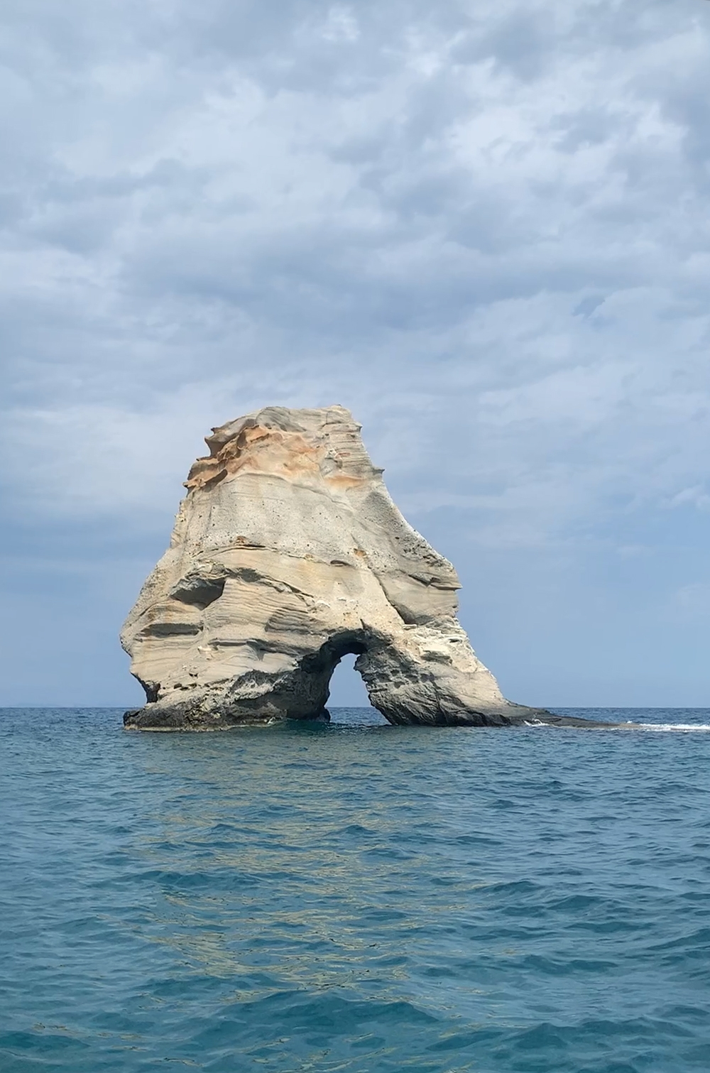 A single pale rock arch in the sea.