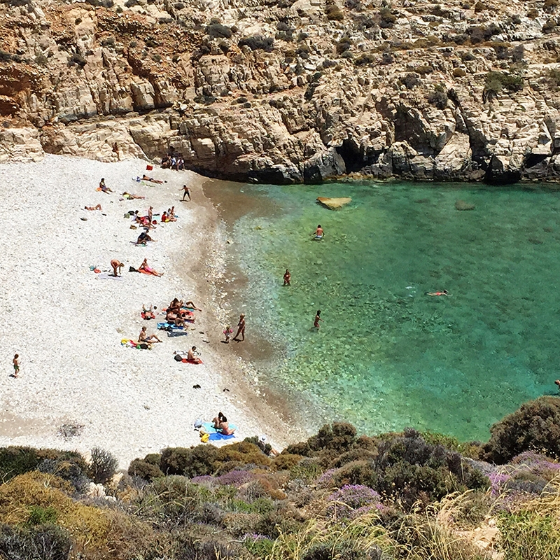 Beachgoers are scattered along a white sandy beach which is set between a rocky cliff landscape