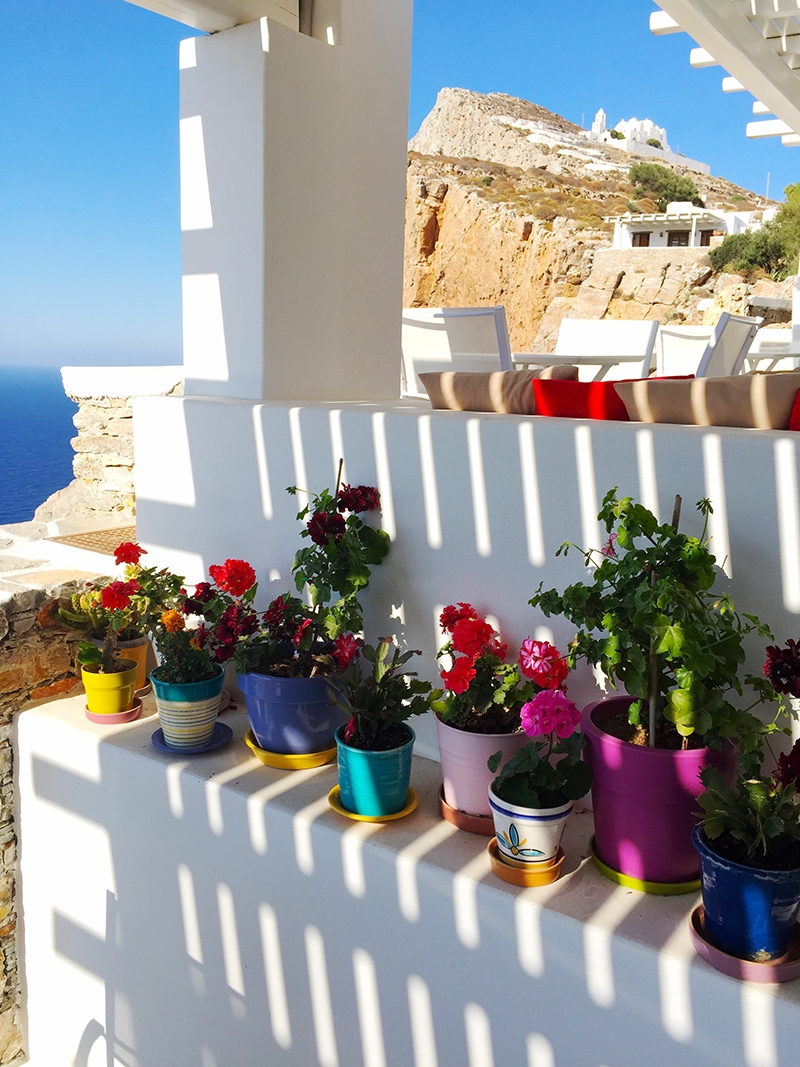 A bright array of potted flowers sitting along a white balcony. Terracotta cliffs and the deep blue ocean sit in the background