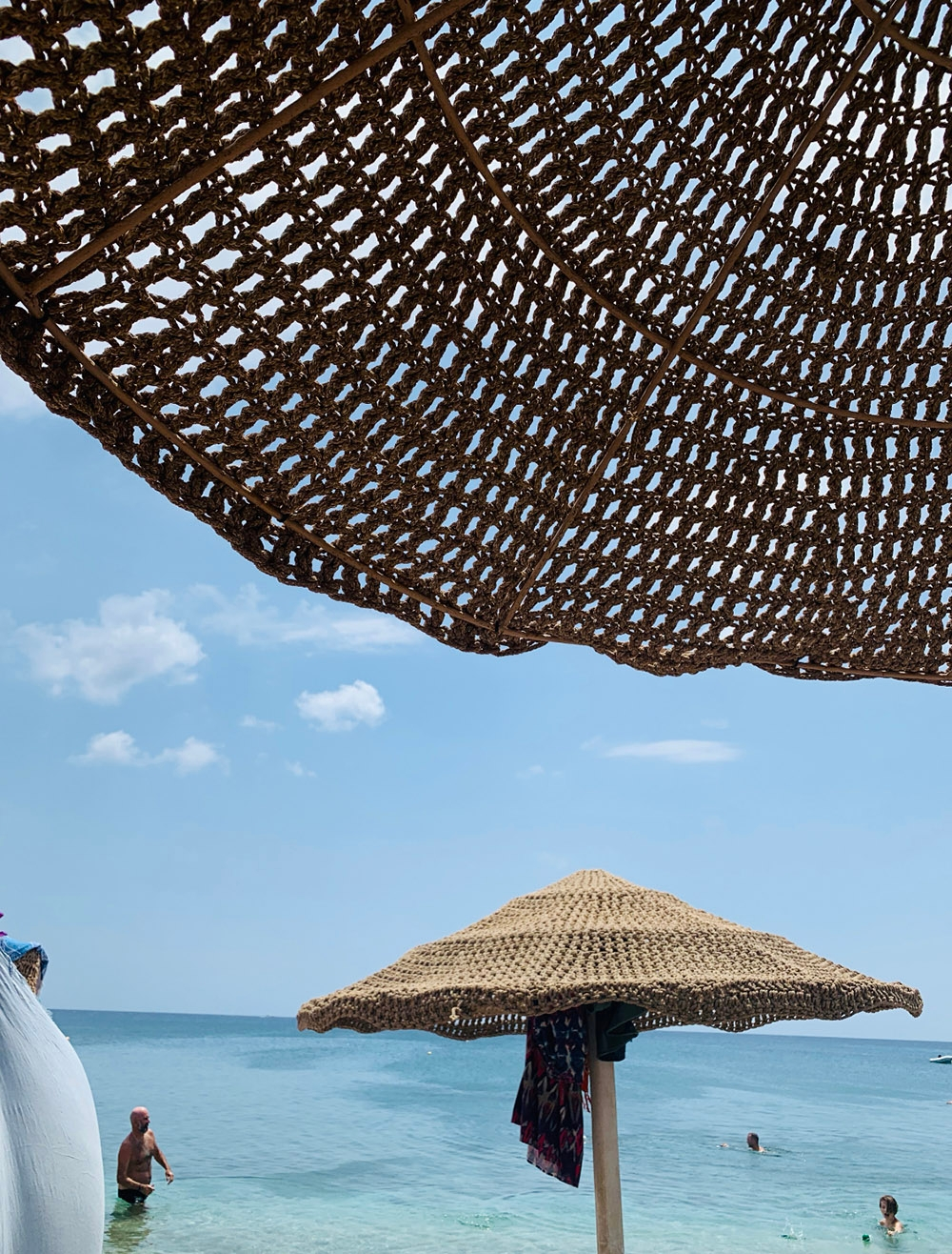 Laying under a beach umbrella facing the clear ocean.