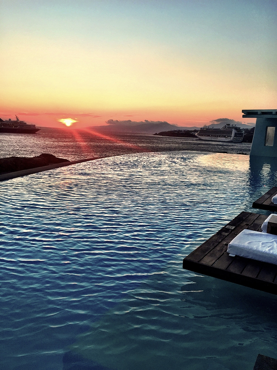 An infinity pool blends into the ocean over the horizon at sunset