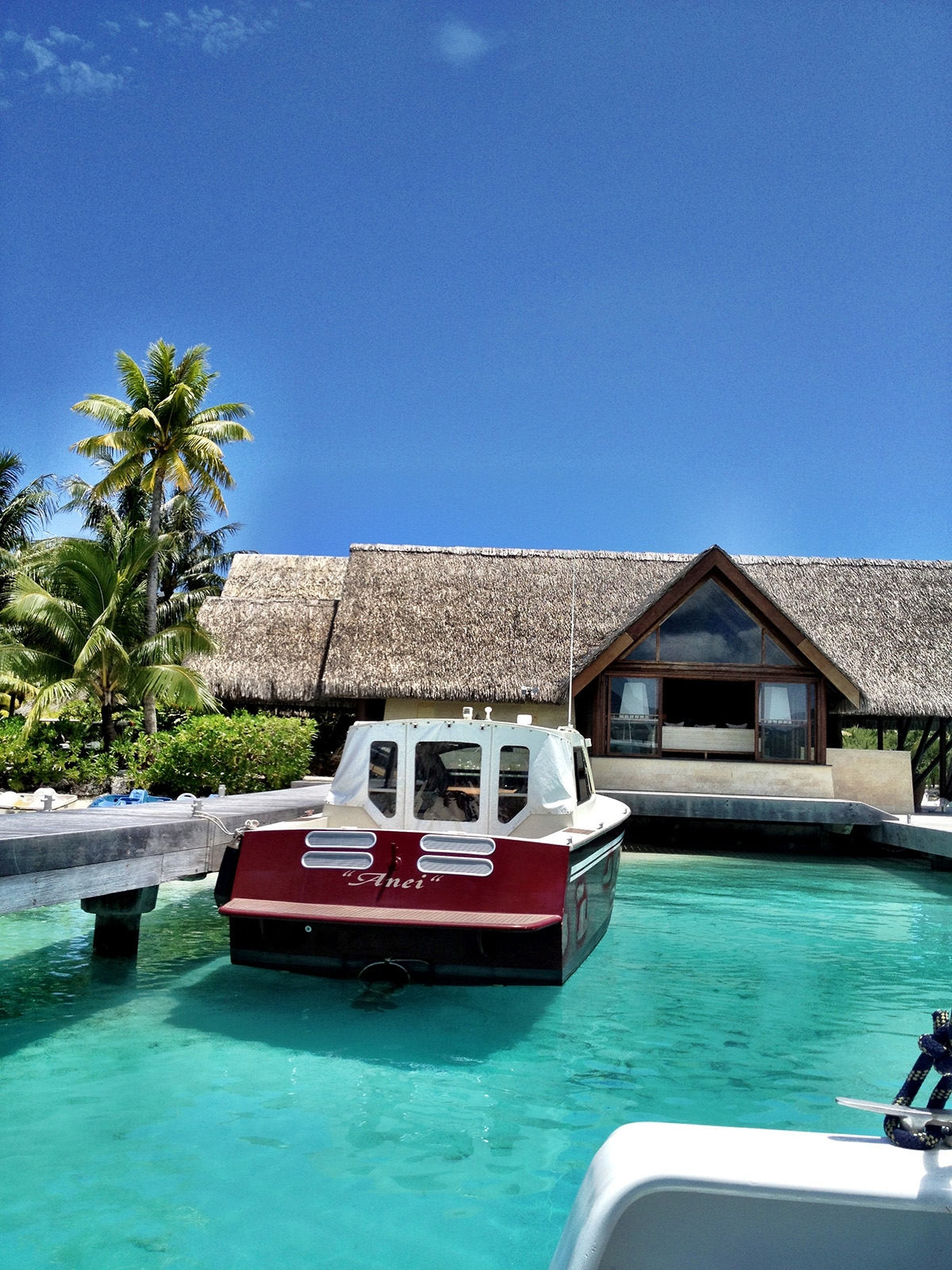 A large red and white boat sits moored in the clear sea alongside an ocean villa