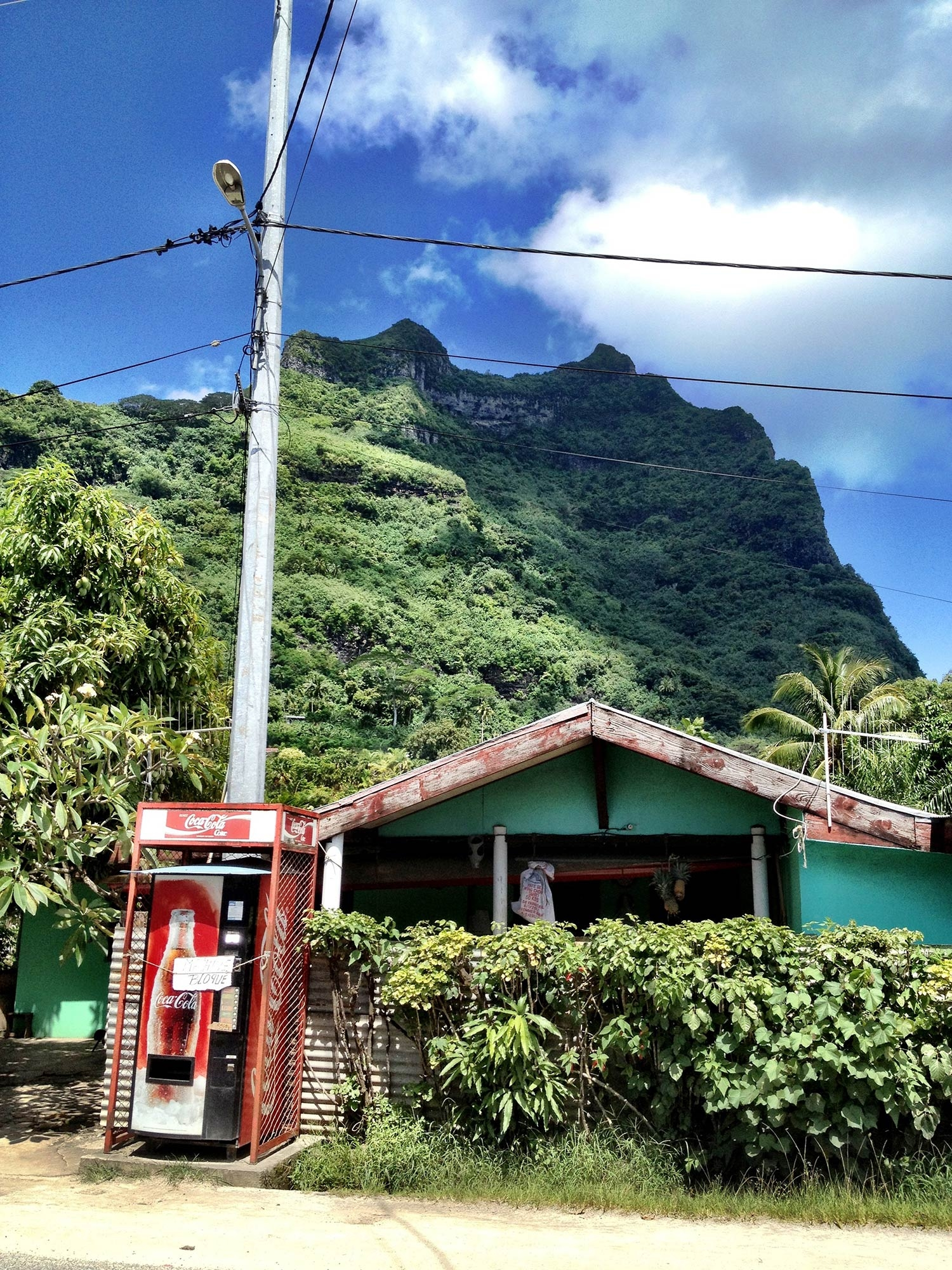 A turquoise building with red trims sits behind a faded coca cola machine and beneath a tall mountain